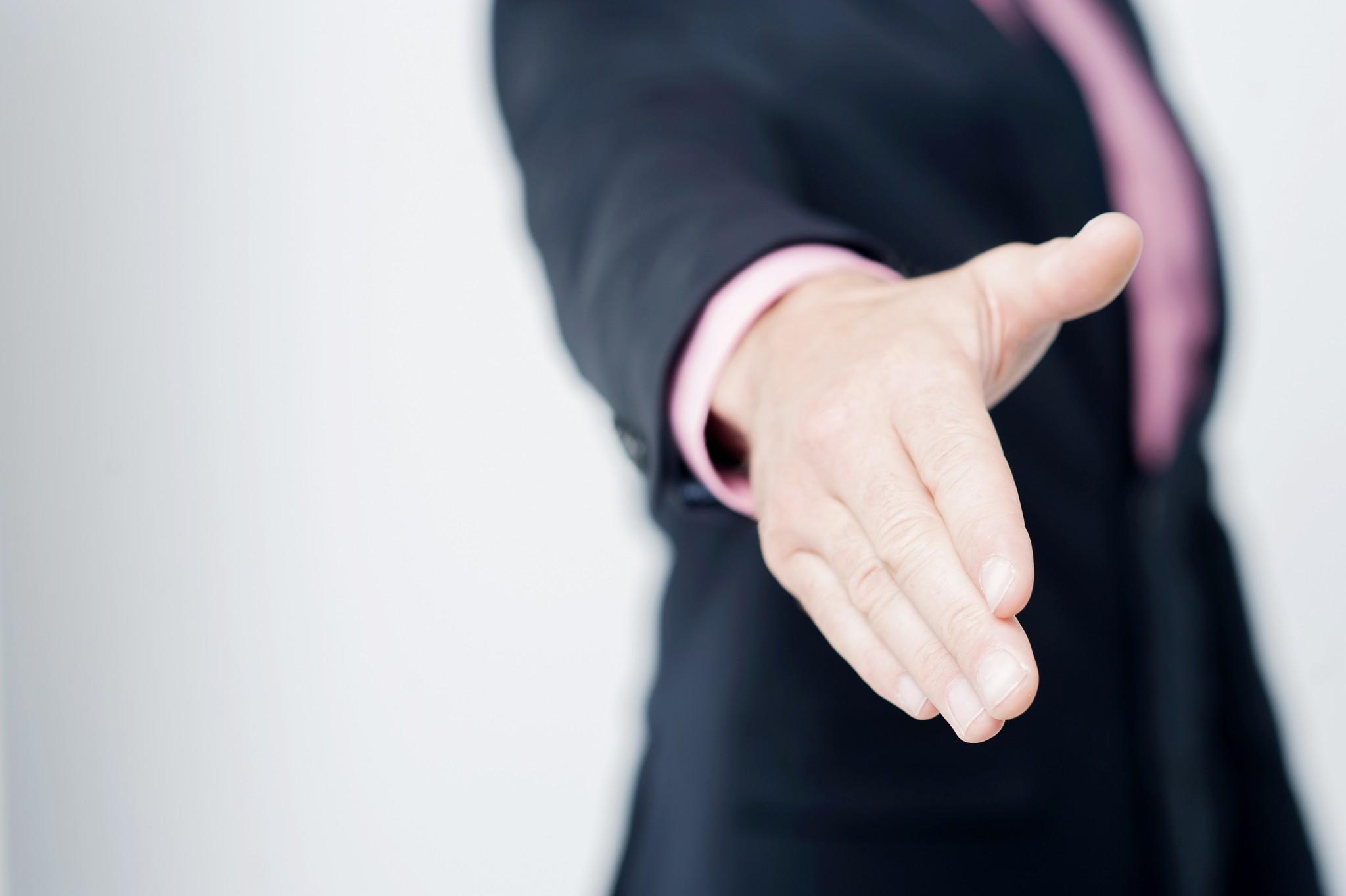 bigstock-Man-Offering-A-Handshake-Gree-79597891